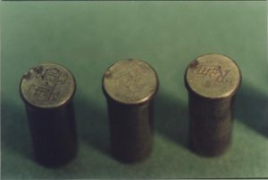 Photograph of the left 3 cases.  The double firing pin strike supports Mr. Waller's, and witnesses, testimony that a warning shot was fired and, after a paause, the revolver was fired until ammunition expended.