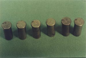 Photograph of the 6 cartridge cases recovered from Mr. Waller's revolver. Note the double firing pin strike on the left most case.