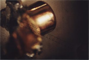 This photograph is of a recovered bullet in this case. Note that the expansion deformation makes mounting of the sample in a microscope extremely problematic. Also, the deformation negates the possibility of using a high enough magnification (with its extremely short focal length, requiring the lens to be closed than four hundredths of an inch) to detect individual striations on the bullet of less than .001 inches, smaller than one/fifth the thickness of the paper on which this is printed.